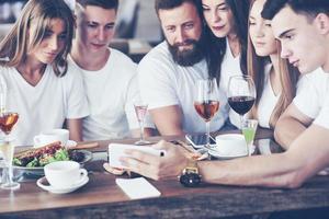 un groupe de personnes fait une photo de selfie dans un café. les meilleurs amis se sont réunis à une table pour manger des pizzas et chanter diverses boissons