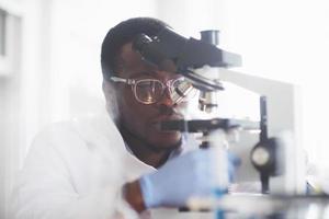 le scientifique travaille avec un microscope dans un laboratoire effectuant des expériences et des formules. photo