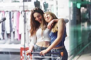 les jeunes femmes s'amusent avec un panier de supermarché le soir. jolie jeune femme passe du temps ensemble au centre commercial photo