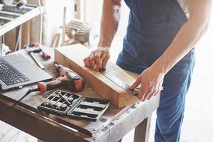 un homme travaille dans une menuiserie, travaillant avec un arbre. photo