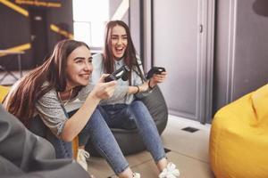 des soeurs jumelles jouent sur la console. les filles tiennent des joysticks dans leurs mains et s'amusent photo