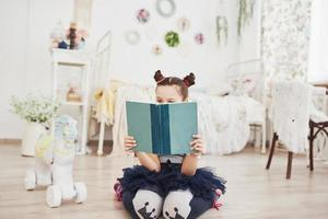 mignonne petite fille enfant lisant un livre dans la chambre. enfant avec couronne assis sur le lit près de la fenêtre photo