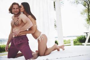 beau mec de couple sexy et fille portant des maillots de bain quand sur la plage. allongé romantiquement sur le sable. photo
