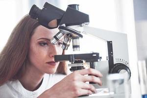 assistant de laboratoire avec ampoule de verrerie de laboratoire de microscope avec des produits chimiques. photo