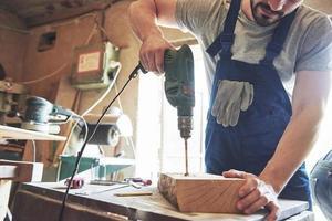 le maître travaille dans un studio et perce un trou dans une planche de bois. photo