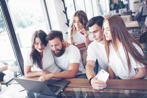 un groupe de jeunes avec des gadgets et un ordinateur portable organise un brainstorming et communique entre eux. le concept de développement d'une jeune entreprise photo