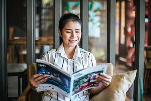 Belle femme lisant un magazine au café photo
