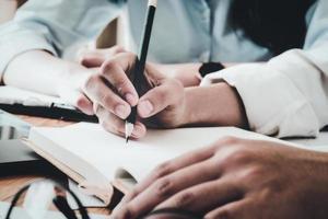 les consultants de l'entreprise prennent des notes lors de la réunion pour faire des plans pour développer la reprise des affaires de l'entreprise. photo