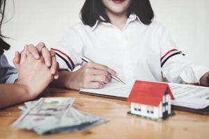le client tient un stylo et lit les conditions afin de signer un contrat d'achat de maison avec des documents d'assurance habitation avec le vendeur. photo