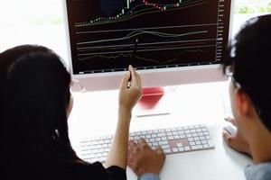 un expert en investissement pointe un stylo sur un moniteur de tablette pour analyser le marché boursier et vous apprendre à réaliser un profit. photo