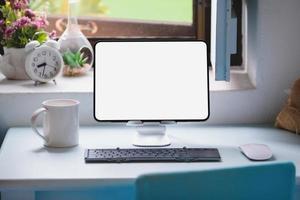 tablette pour travailler sur un bureau en bois, un écran de tablette vierge peut ajouter du texte ou d'autres médias. photo