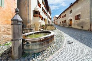 Vieille fontaine dans le village alpin suisse de guarda en engadi photo