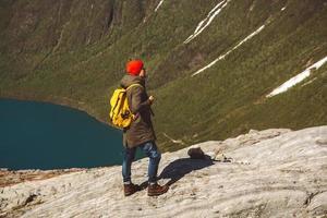 homme avec un sac à dos debout sur un rocher sur fond de montagne et de lac photo