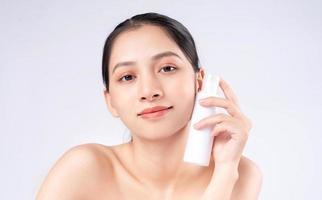 jolie jeune femme asiatique avec une peau jeune. soins du visage, traitement du visage, peau de beauté femme isolée sur fond blanc. cosmétologie, beauté de la peau et concept cosmétique photo
