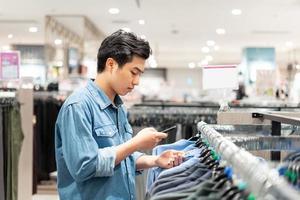 un homme asiatique intelligent utilisant son téléphone ramasse des vêtements dans le magasin de vêtements du centre commercial, photo