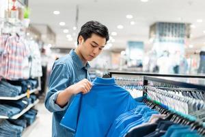 l'homme asiatique intelligent choisit des vêtements dans le magasin de vêtements du centre commercial, photo