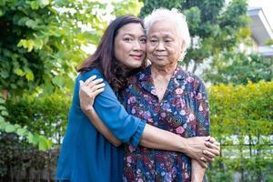femme âgée asiatique avec soignant marchant avec plaisir dans le parc naturel. photo