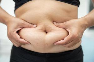 une femme asiatique en surpoids montre un gros ventre au bureau. photo