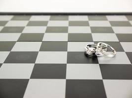 bague en diamant avec échecs roi et reine sur le plateau, concept de mariage. photo