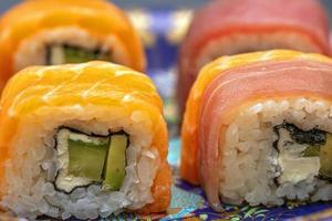 rouleaux de sushi californiens avec avocat, concombre et fromage enveloppés de saumon et de thon photo