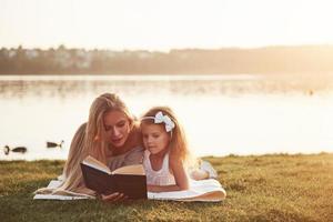 mère avec un enfant lit un livre sur l'herbe photo