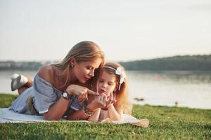 jolie jeune mère heureuse allongée avec sa jolie fille sur l'herbe dans le parc. photo
