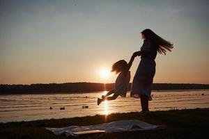 maman joue avec son bébé en vacances près de l'océan, silhouettes au coucher du soleil photo