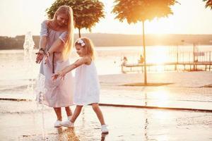 une femme jouant avec un enfant près de l'océan dans le parc au coucher du soleil photo