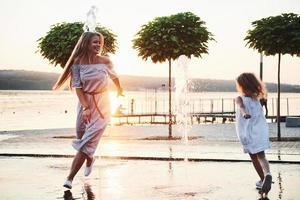 mère avec bébé près de la fontaine au coucher du soleil photo