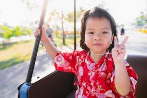 fille heureuse monte dans une voiturette de golf dans le parc au printemps. doux sourire bébé lève deux doigts. adorable enfant vêtu d'une robe rouge de style japonais. enfants de 1 à 2 ans. photo