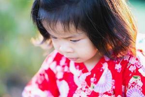 gros plan, adorable fille asiatique de 1 à 2 ans regarde son chemin. un bébé joyeux porte une robe rouge de style japonais. pendant l'été ou le printemps. photo
