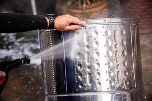 les gens utilisent un tuyau d'injection à haute pression pour laver le réservoir de lavage en acier inoxydable jusqu'à ce qu'il soit propre. réservoir de lavage en acier inoxydable argenté qui est lavé par des personnes. photo