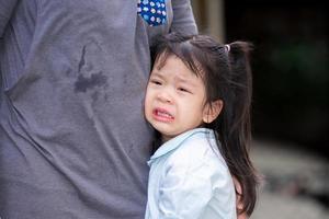 adorable fille asiatique pleure avec des larmes sur les joues. enfant reposait sur le ventre de sa mère. les enfants souffrent de chagrin d'amour. un enfant de 4 ans porte des chemises bleu clair. photo
