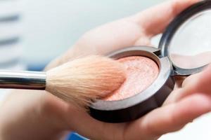 gros plan sur des mains de femme tenant une brosse à maquillage et une boîte à fard à joues photo