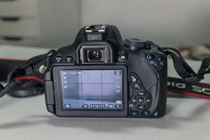 Gros plan de l'appareil photo reflex numérique noir moderne sur tableau blanc