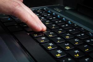 homme tapant sur un clavier avec des lettres en hébreu et en anglais photo