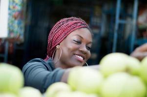 jeune femme souriante choisissant une pomme au marché de rue. photo