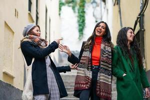 groupe multiethnique de trois femmes heureuses marchant ensemble à l'extérieur photo