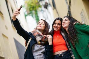 groupe de trois femme heureuse marchant ensemble à l'extérieur photo
