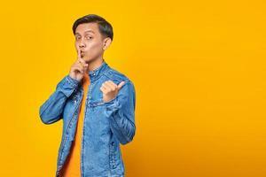 signal de l'homme asiatique au silence et pointant vers le côté sur fond jaune photo