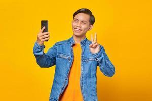 portrait d'un homme asiatique souriant et montrant un signe de paix tout en prenant un selfie sur mobile isolé sur fond jaune photo
