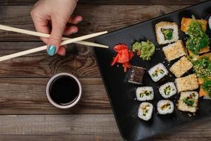 Sushi. main avec des baguettes photo