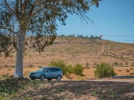 Véhicule tout-terrain suv gris garé à l'ombre d'un eucalyptus sur un chemin de terre photo