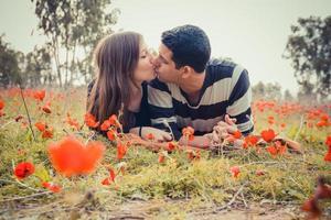 Jeune couple s'embrassant en position couchée sur l'herbe dans un champ de coquelicots rouges photo