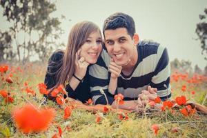 Jeune couple allongé sur l'herbe dans un champ de coquelicots rouges et souriant à la caméra photo