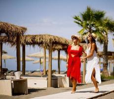 deux jeunes femmes marchant sur une plage en été photo