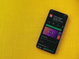 gouttes - page de magasin de l'application d'apprentissage des langues sur l'écran d'un smartphone mobile noir sur fond de tissu jaune photo