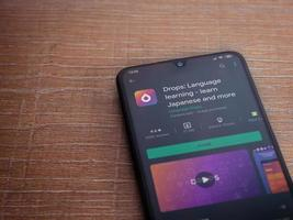 gouttes - page de magasin de l'application d'apprentissage des langues sur l'écran d'un smartphone mobile noir sur fond de bois photo