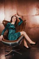 jolie fille brune vêtue d'une robe de velours, assise dans un fauteuil en cuir photo