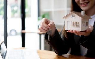 séduisante jeune femme agent immobilier ou agent immobilier tenant une chaîne de clés de maison et un modèle de maison. arrière-plan flou. photo